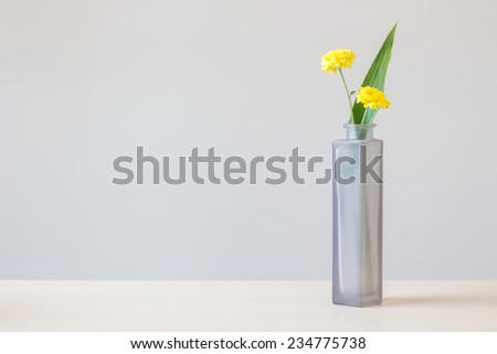 Fresh yellow flowers in glass bottle on wood table - stock photo