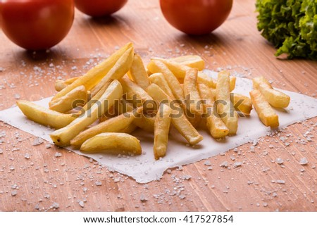fresh yellow fries on a wooden table with sea salt