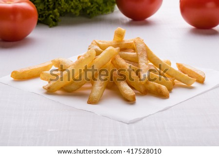 fresh yellow fries on white table with vegetables - stock photo