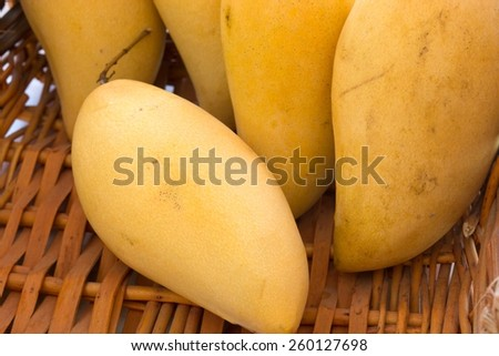 Fresh yellow mango in the Basket on white background - stock photo