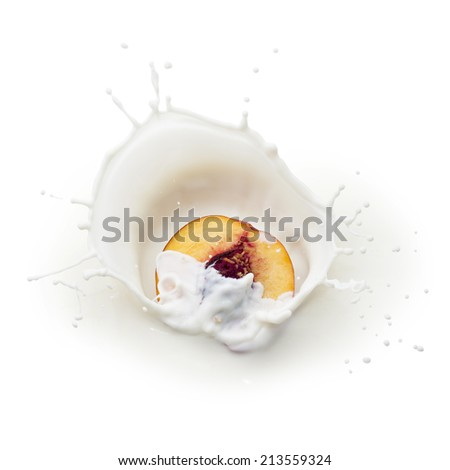 Fresh yellow peach half falling into milk with splash - stock photo