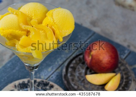 Fresh yellow peach ice-cream in glass cone on the beach on gray wooden background, summer vacation concept - stock photo