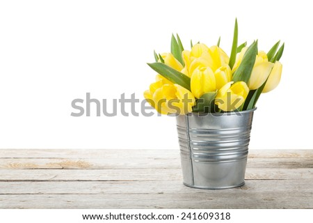 Fresh yellow tulips bouquet over wooden table. Isolated on white background - stock photo