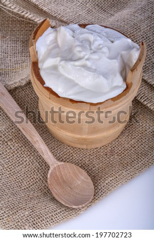 fresh yogurt in a wooden bowl on a linen background