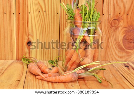 Fresh young carrots in jar and on wood - stock photo