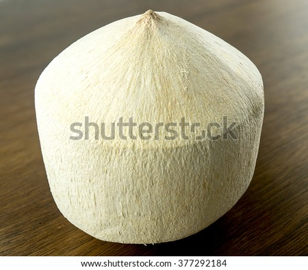 Fresh young coconut with white fibrous husky shell - stock photo