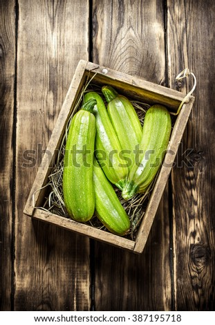 Fresh zucchini in an old box. On wooden background. - stock photo