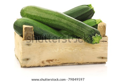 fresh zucchini's (Cucurbita pepo) in a wooden box on a white background