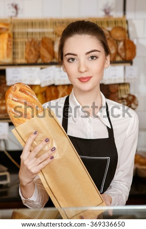 Freshest bread in town. Vertical portrait of a young baker woman holding fresh bread smiling to the camera  - stock photo