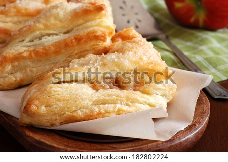 Freshly baked apple turnovers on wooden tray with antique pie server and apple in background.  Rustic still life with natural directional lighting and shallow dof.  - stock photo