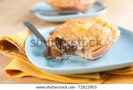 Freshly Baked Australian Meat Pies with Beef and Mashed Potatoes Served on Blue Plates - stock photo