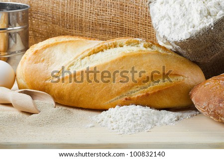 Freshly baked baguette and bread on wooden cutting board, sack of flour, rolling pin, sieve - stock photo