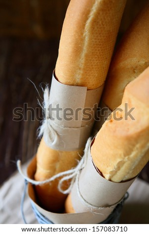 freshly baked baguettes tied with paper, food - stock photo