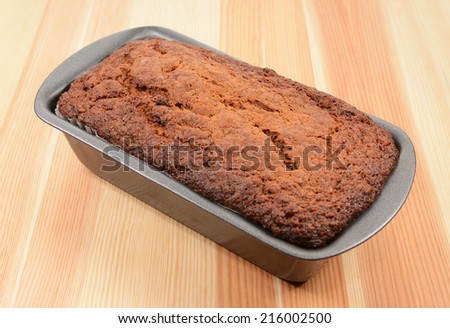 Freshly baked banana bread in a loaf tin on a pine table - stock photo