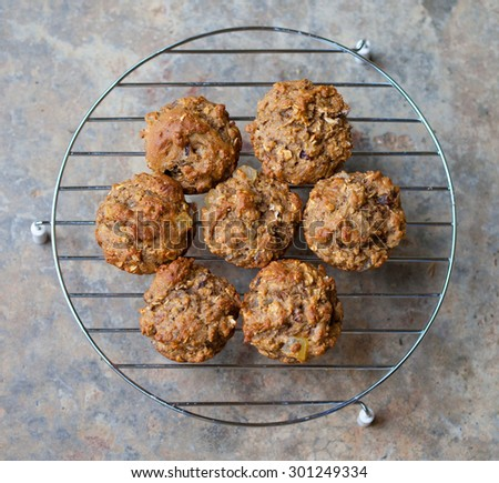 Freshly baked bran muffins cooling on a rack - stock photo