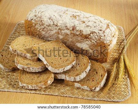 Freshly baked bread and wheat on table - stock photo