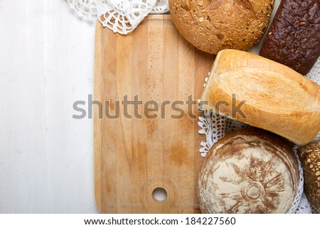 Freshly baked bread and wooden board - stock photo