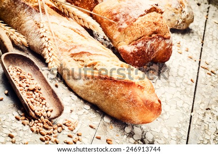 Freshly baked bread in rustic setting with copyspace - stock photo