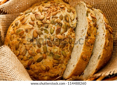 Freshly baked bread with seeds in basket - stock photo