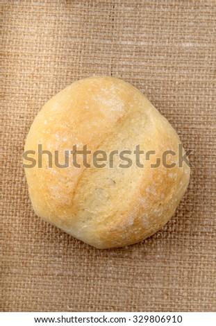 freshly baked bun on a hessian cloth - stock photo