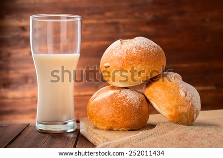 Freshly baked buns and glass of milk on wooden board - stock photo