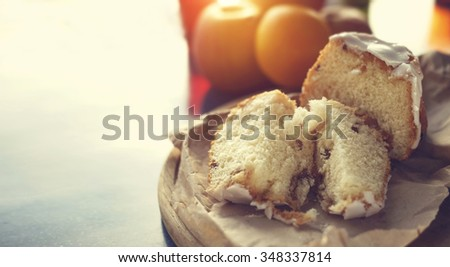 Freshly baked buns with raisins. Tasty bread and fruit for breakfast. Fresh pastries and fruit for breakfast in the morning. Concept - morning, sun light, fresh cakes, happiness, delicious smell. - stock photo