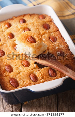 Freshly baked cake with almonds basbousa close up in baking dish. vertical