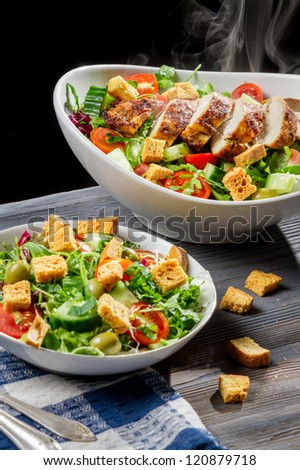 Freshly baked chicken and salad Caesar - stock photo