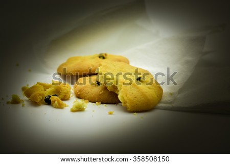 Freshly baked chocolate chip cookies on non-stick cookie sheet with cooling rack in soft focus in background. Macro with extremely shallow dof. - stock photo
