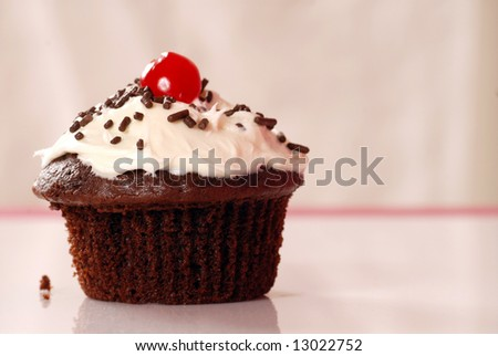 Freshly baked chocolate cupcake with vanilla buttercream, sprinkles and a cherry - stock photo
