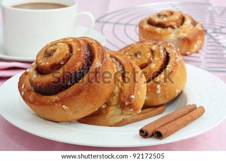 Freshly baked cinnamon rolls with a cup of coffee. - stock photo