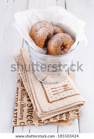 Freshly baked cinnamon sugared doughnuts in wrapping paper in the metal bucket on white wooden background. Rustic still life - stock photo