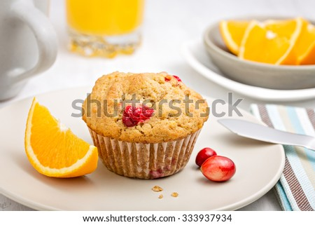 Freshly baked cranberry orange muffin on a plate for breakfast - stock photo