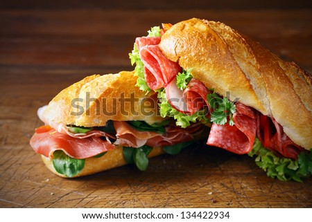 Freshly baked crisp golden baguettes filled with ham and basil or lettuce and salami on a wooden surface - stock photo