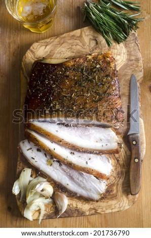 Freshly baked crispy pork belly on a cutting board - stock photo