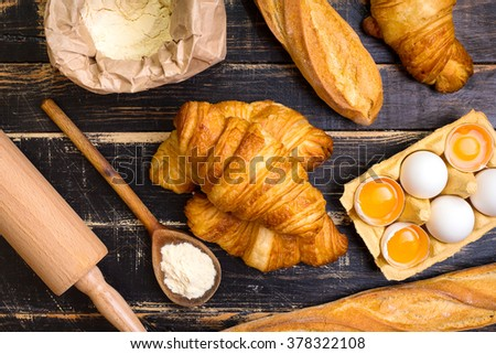 Freshly baked croissants and baguettes with flour, rolling pin, spoon, eggs and egg yolks in a carton tray on the dark wooden background. Ingredients for baking. Top view - stock photo
