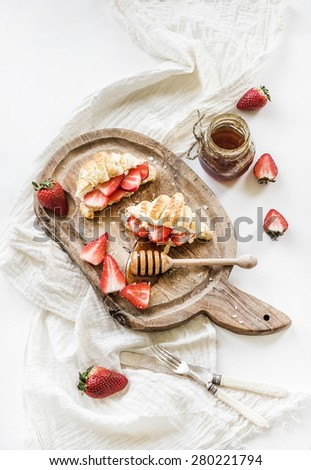 Freshly baked croissants with strawberries, mascarpone and honey on rustic wooden board over white backdrop, top view - stock photo