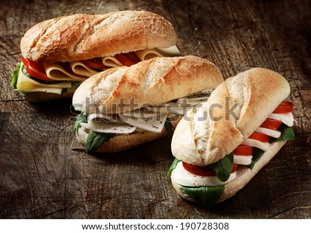 Freshly baked crusty golden vegetarian baguettes in a bakery with a variety of cheese, herb and salad fillings on a rustic wood background, closeup view - stock photo
