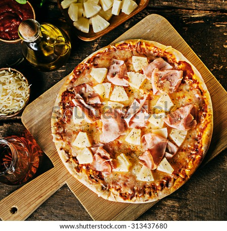 Freshly baked crusty ham and pineapple Hawaiian pizza on a wooden board surrounded by ingredients in individual dishes on a rustic wood kitchen counter, overhead view - stock photo