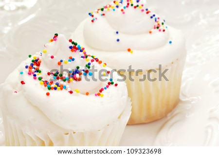 Freshly baked cupcakes with swirls of vanilla frosting and sprinkles on decorative plate.  Macro with shallow dof.  Selective focus on sprinkles of front cupcake. - stock photo