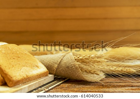 Freshly baked delicious bread on a rustic wooden background with copy space, flat lay.