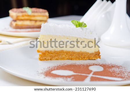 Freshly baked delicious slice of cheesecake with a biscuit base topped with cream presented on a plate with crossed spoon outline in chocolate powder - stock photo