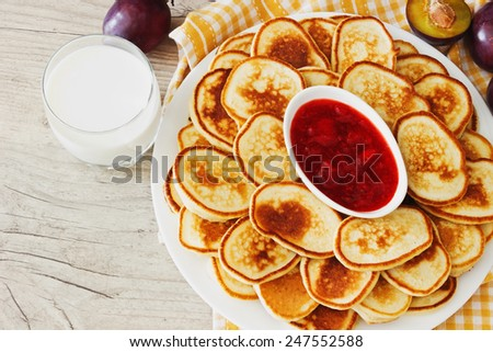 freshly baked fritters, fruit and a glass of milk on wooden background. traditional european cuisine - stock photo
