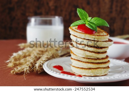 freshly baked fritters on a plate, strawberry jam, wheat stalks, leaves of mint and milk on the table. traditional european cuisine. selective focus - stock photo