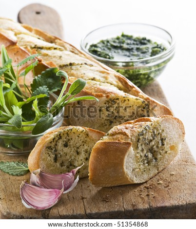 Freshly baked garlic bread with herbs close up - stock photo