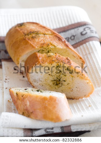 Freshly baked garlic bread with herbs close up. Selective focus - stock photo