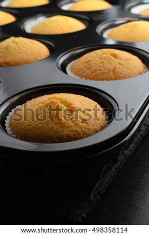 Freshly baked golden cupcakes, just removed from oven.  In paper cases inside black bun tin, resting on slate.
