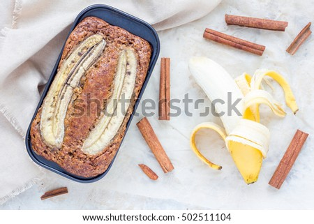 Freshly baked homemade banana cinnamon muffins with slice of banana on top in baking dish, top view