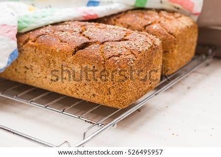 Freshly baked homemade bread lying on metal grille. Natural bread made in kitchen.
