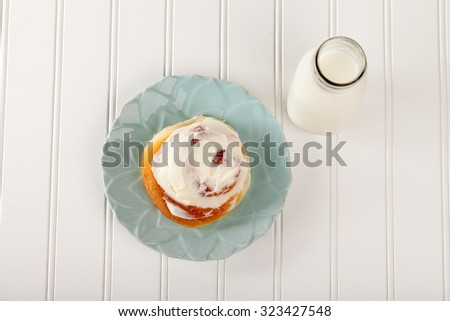 Freshly baked homemade cinnamon roll with cream cheese buttercream frosting and an antique bottle of milk top view - stock photo